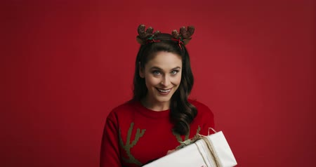 výstřední : Woman with Christmas present on red background Dostupné videozáznamy