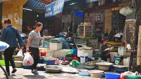 genuíno : Hanoi,Vietnam - May 15,2018 : Busy local daily life of the morning street market in Hanoi, Vietnam. A busy crowd of sellers and buyers in the market.
