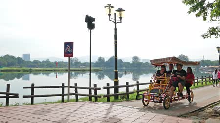 malásia : Kuala Lumpur, Malaysia - June 1,2018 : People can seen cycling 4 wheel bicycles to explore the beautiful of the Titiwangsa Lake Gardens in the morning.