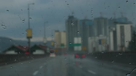 drive through : Looking through windshield at defocused traffic with windshield wipers on. Stock Footage