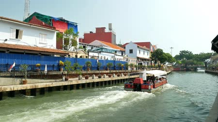 colonial : Malacca, Malaysia - May 18, 2019:  Riverside scenery of a cruise full of passengers crossing by the Malacca River. It has been listed as UNESCO World Heritage Site since 772008.
