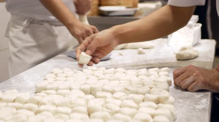 準備する : Close-up of making xiao long bao, dough knead and divided into small pieces.