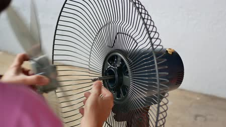 Kuala Lumpur,Malaysia -  Nov 14,2019 : Close-up view of a woman installing the table fan.