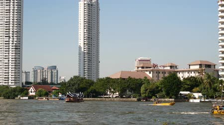 Bangkok,Thailand - November 13,2019 : People can getting around the famous riverside area of Bangkok with its many historical attractions, temples and architecture by river boats and ferries. Stock mozgókép