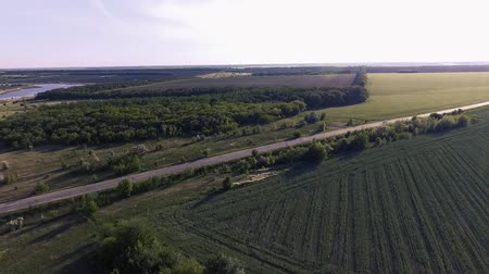 agricultural lands : flight over the fields and the old road with the traveling cars at sunset. Spring season outside the city. Ukraine. Europe. Stock Footage