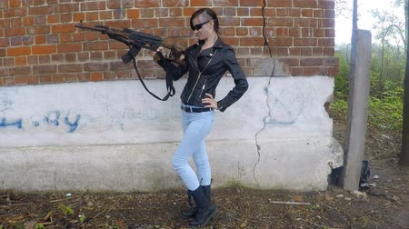 couro : Girl in a leather jacket posing with Kalashnikov