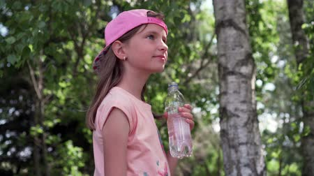 ecologically : Thirsty girl drinking water in a park 4K