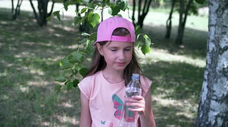 susuzluk : Thirsty girl drinking water out of a plastic bottle 4K