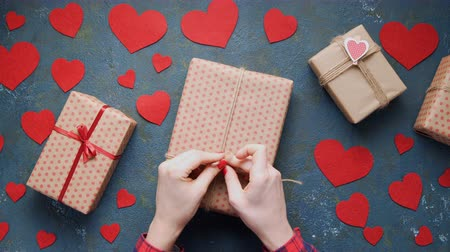 položit : Womans hands packing Valentines Day holiday gift box concept of romantic love. Overhead shot. Vintage blue table with red hearts decorations flat lay. Dostupné videozáznamy