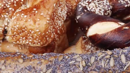 bagietka : mix of fresh homemade baguettes , pretzels and wheat loafs, on wooden table Wideo