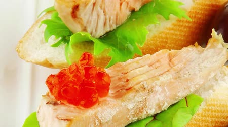 икра : pieces of salmon and red caviar on baguette with olives