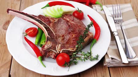 нездоровое питание : savory : roasted beef spare rib on white dish with cutlery thyme pepper and tomato on wooden table Стоковые видеозаписи