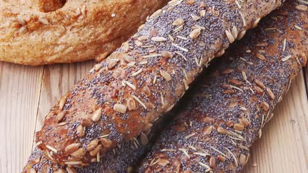хлеб : delicacy french rye breads and baguettes topped with sunflower and poppy seeds over wooden table Стоковые видеозаписи