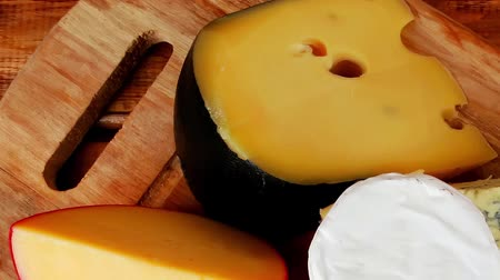 emmental : dairy product many delicious aged cheeses on wooden plate