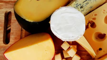 pieces of cheese : dairy food cheeses on wooden plate over table