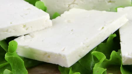 pieces of cheese : feta cheese on wooden plate with salad