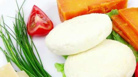 soft cheeses : french cheeses : delicatessen aged cheeses with soft feta chops served on white plate with slices isolated on white background