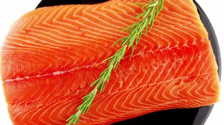 carne : fresh raw salmon fillet on black over white and rosemary
