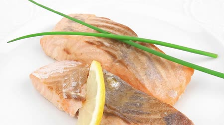 carne : healthy fish cuisine : baked pink salmon steaks with green onion and lemon on white dish isolated over white background