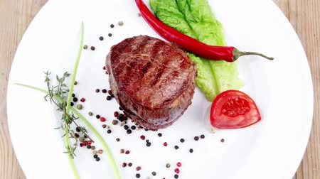 говядина : grilled beef fillet pieces with thyme red hot chili pepper and tomato on white plate over wood