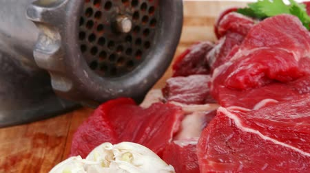 cielęcina : fresh raw beef meat slices over a wooden board with dill   green  and red hot peppers  and grinder isolated over white backkground Wideo