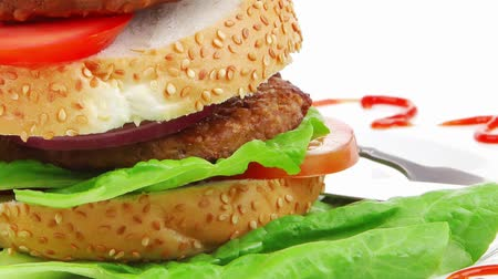 фастфуд : big double grilled hamburger on ceramic plate isolated  over white background Стоковые видеозаписи