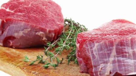 schab : fresh red meat : two raw beef fillet chops on wooden board with small thyme twig ready to prepare . isolated over white background Wideo