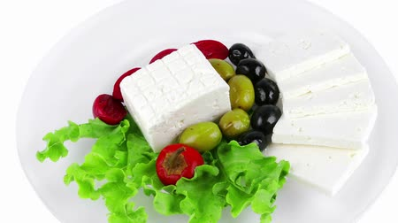 pieces of cheese : served greek dinner on dish with vegetables