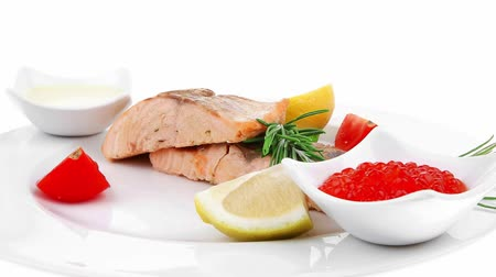 soja : savory fish portion : norwegian salmon fillet pieces roasted with chinese onion  lemon  rosemary twig and red caviar on white dish isolated over white background Vídeos