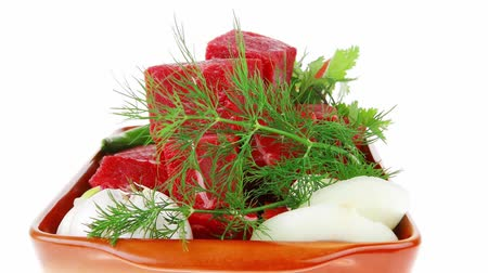 кинза : uncooked fresh beef meat chunks on ceramic bowls with vegetables and greenery isolated over white background