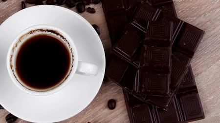 italian food : sweet hot drink : black coffee with beans in a white bag on a wooden table with stripes of dark chocolate and copper cezve Stock Footage