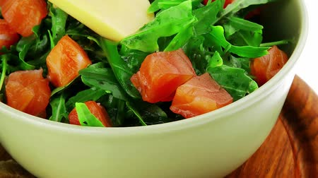 fresh cheeses : green salad with salmon and tomatoes in green bowl