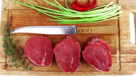 schab : raw fillet chops : fresh beef meat with thyme and red hot dry pepper on wooden plate . isolated over white background Wideo