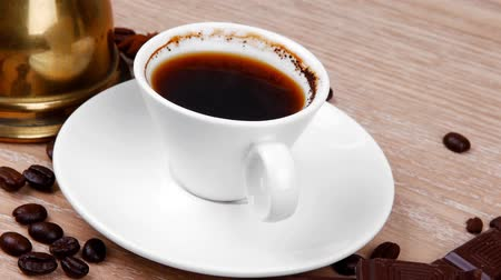 martwa natura : sweet hot drink : black Turkish coffee in small white mug with coffee beans spilled on a wooden table with stripes of dark chocolate and copper Arab Cezve full coffee