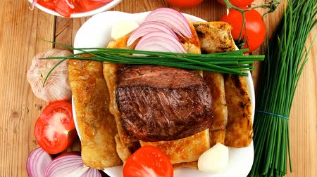 asal : roast meat : beef ( lamb ) steak garnished with onion   tomatoes salad and chives  on wooden table