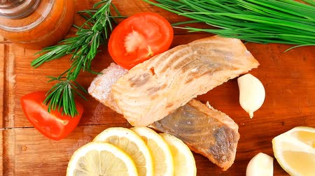 biber : sea food : roasted pink salmon fillet with chinese onion  cherry tomatoes pieces  pepper grinder  rosemary twigs and lemon on wooden board isolated over white background