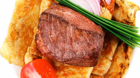 gourmet : roast meat : beef ( lamb ) steak garnished with onion   tomatoes salad and chives isolated over white background