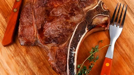 нездоровое питание : meat food : roast rib on wooden plate with thyme isolated over white background Стоковые видеозаписи