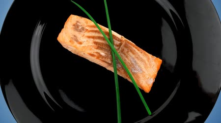 side view : healthy fish cuisine : baked pink salmon steaks with green onion on black dish isolated over white background Stock Footage
