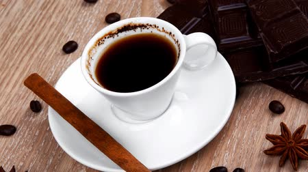 italian food : sweet hot drink : black coffee in small white cup with beans on a wooden table with stripes of dark chocolate and cinnamon sticks