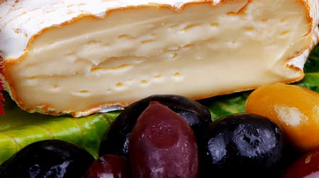 macro fotografia : aged camembert cheese on green salad in white dish over cloth with olives and over wooden table