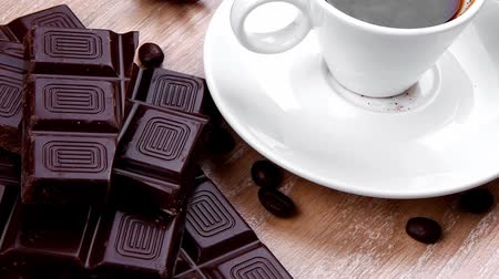 italian food : sweet hot drink : black coffee in small white cup with beans on a wooden table with stripes of dark chocolate and copper cezve Stock Footage