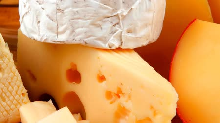 pieces of cheese : many delicious aged cheeses on wooden plate Stock Footage