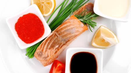золотая рыбка : savory fish portion : norwegian salmon fillet pieces roasted with chinese onion  lemon  rosemary twig and red caviar on white dish isolated over white background Стоковые видеозаписи