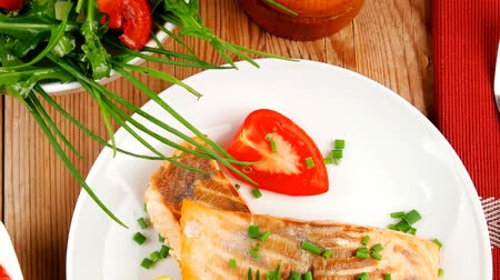 asal : healthy sea food : roasted pink salmon fillet with vegetable salad   chives  lemon  red caviar in white bowl  with pepper in grinder and cutlery on white dish over wooden table