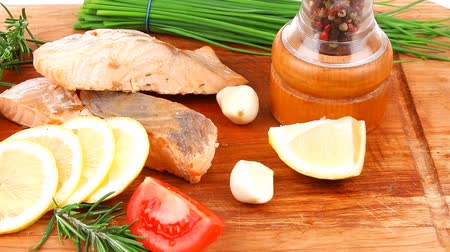 biber : healthy fish cuisine : baked pink salmon steaks with green onion  cherry tomatoes  small pepper grinder  rosemary twigs and lemon on wooden board isolated on white background Stok Video