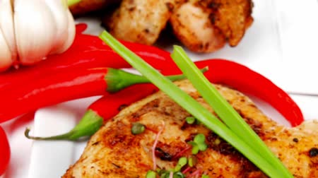eat background : grilled meat : grilled quarter chicken garnished with green sweet peas   red peppers plates over wooden table 1920x1080 intro motion slow hidef hd