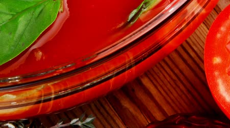 száraz : diet food : hot tomato soup with basil thyme and raw tomatoes in transparent bowl over red mat on wood table ready to eat 1920x1080 intro motion slow hidef hd Stock mozgókép