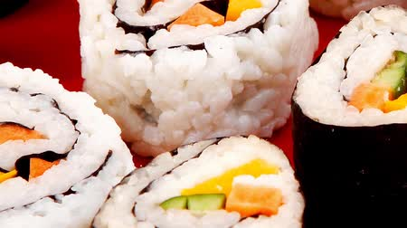 ebéd : Maki Sushi : Maki Rolls and California rolls made of fresh raw Salmon  Tuna and Eel . on red dish with sticks 1920x1080 intro motion slow hidef hd