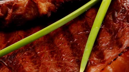 beef dishes : close-up of juicy sirloin beef with pasta tomatoes and green onion on dark dish 1920x1080 intro motion slow hidef hd Stock Footage